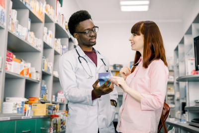 Handsome African male pharmacist talking with a beautiful female client in modern light pharmacy